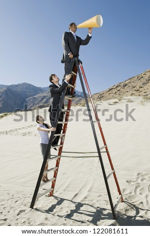 Businessman speaking through megaphone with colleagues standing on ladder in desert - stock photo
