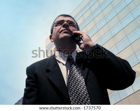 Businessman speaking to the mobile phone in a big city - stock photo