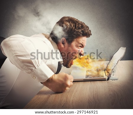 Businessman spits fire and melts the computer - stock photo