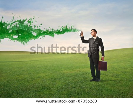 Businessman spraying green paint on a green meadow - stock photo
