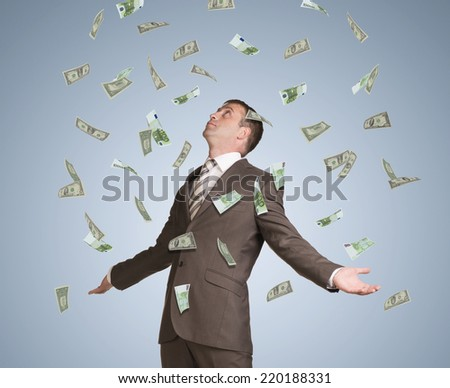 Businessman spread his arms. Money fall from above