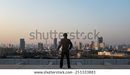 businessman stand on roof top of skyscraper, business concept - stock photo