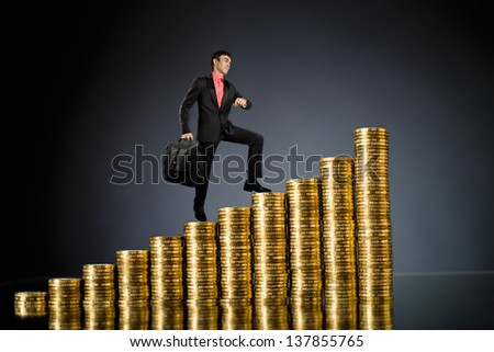 businessman stand on top of  many rouleau gold  monetary  coin, on dark blue background - stock photo