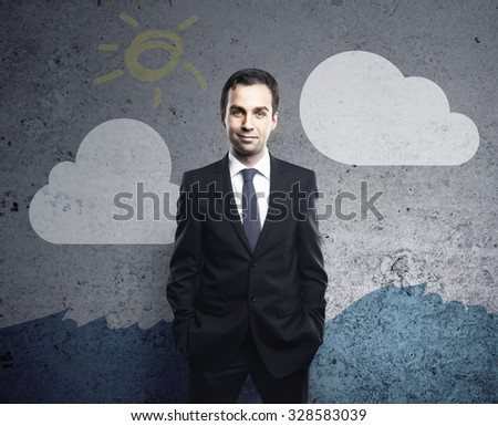 businessman standing against a gray wall with drawing cloud - stock photo