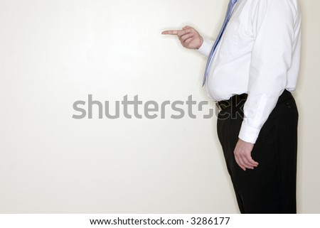 Businessman standing against a white wall points his finger in blame