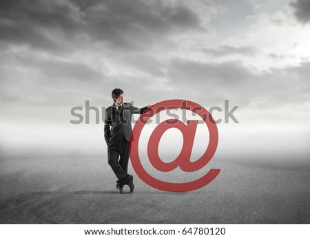 Businessman standing against an at sign - stock photo