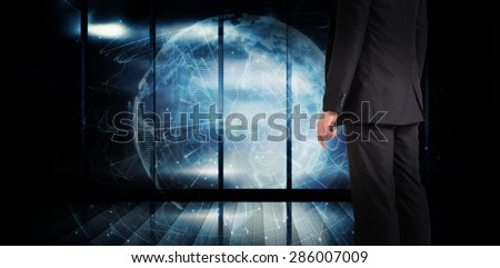 Businessman standing against global technology background in blue