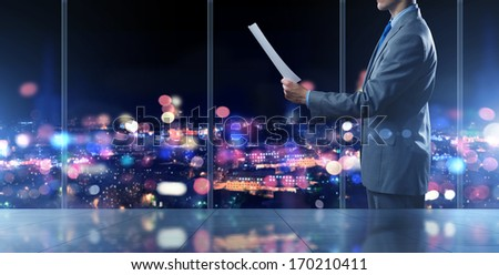 Businessman standing against office window reading documents - stock photo