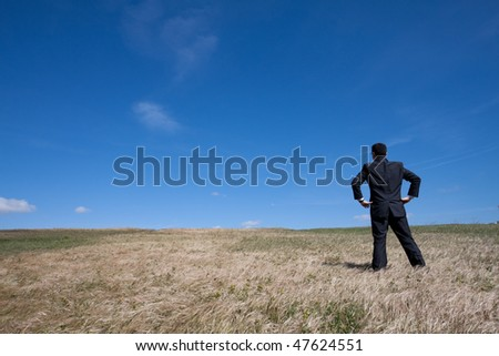 businessman standing alone at the field - stock photo