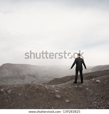 businessman standing alone in the desert - stock photo