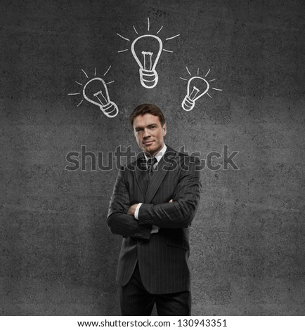 businessman standing and drawing lamps on wall