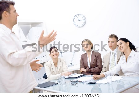 Businessman standing and explaining to four colleagues sitting in front of. - stock photo