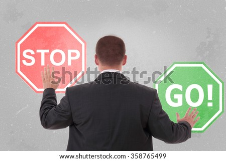 Businessman standing and holding a stop sign and go sign - stock photo