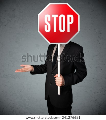Businessman standing and holding a stop sign in front of his head - stock photo