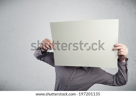 Businessman standing and holding in front of his head a white paper with copy space - stock photo