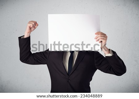 Businessman standing and holding in front of his head a white paper with copy space