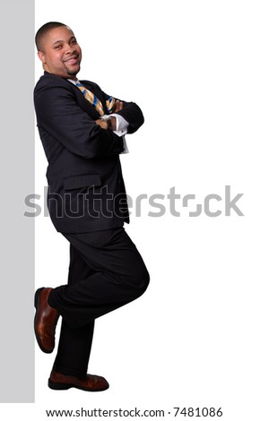 Businessman standing and leaning on wall isolated over a white background. - stock photo