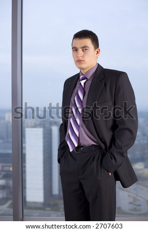 Businessman Standing and Looking at the Camera. There's Big Window With Big City View Behind Him.