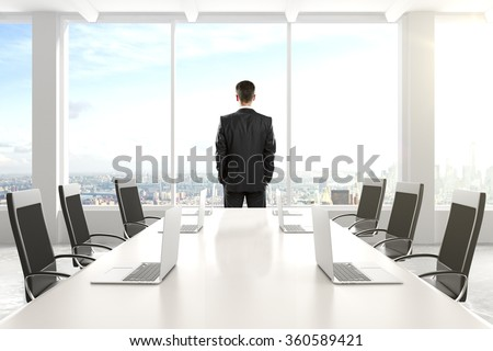 Businessman standing and looking out the window in the conference room with a table and laptops 3D Render - stock photo