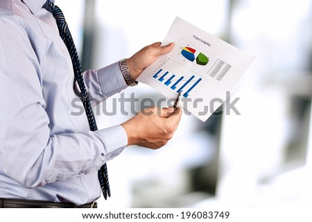 Businessman standing and showing graphics, diagram. Presentation. - stock photo