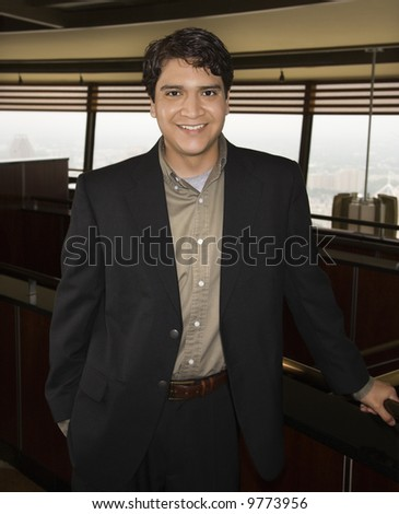 Businessman standing and smiling at viewer. - stock photo