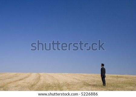 Businessman standing and thinking in the nature