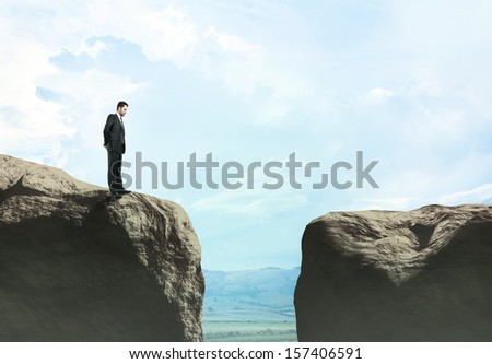 businessman standing at big rock - stock photo