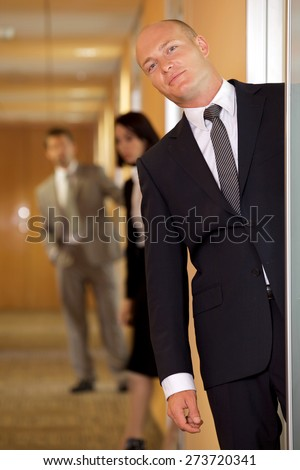 Businessman standing at door while colleagues in background - stock photo
