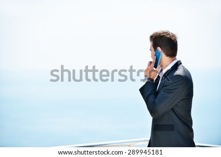 Businessman standing at the balcony near sea under blue sky