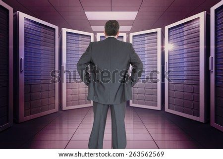 Businessman standing back to the camera with hands on hip against server room