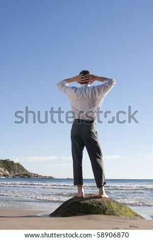 Businessman standing barefoot on a rock at the sea - stock photo