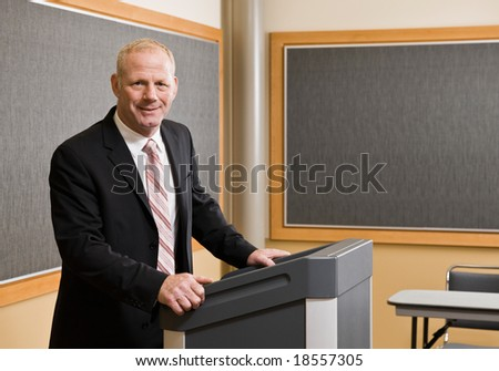 Businessman standing behind podium preparing to give presentation in conference room - stock photo