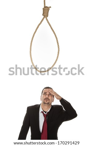 Businessman standing below a hangmans noose contemplating suicide as a result of a business failure or crisis or aware of the punishment for any criminal activity - stock photo