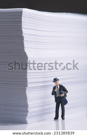 Businessman standing beside an office paper  stack - stock photo