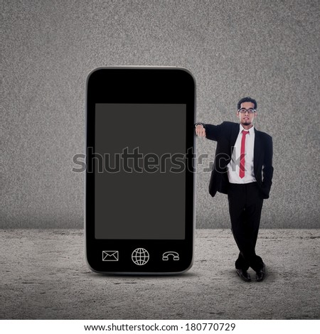 Businessman standing beside large smartphone on grey background - stock photo