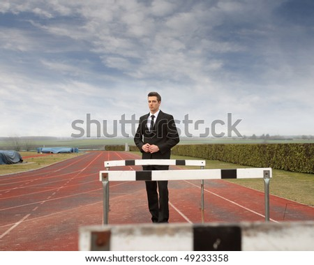 Businessman standing between some obstacles on a running court