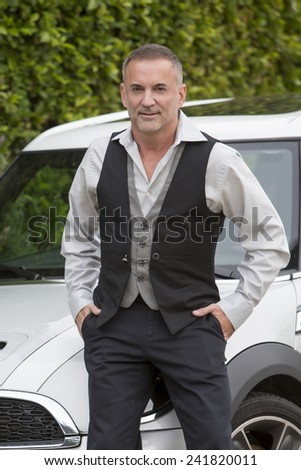 businessman standing by a car and smiles