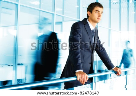 Businessman standing by banisters with walking people on background