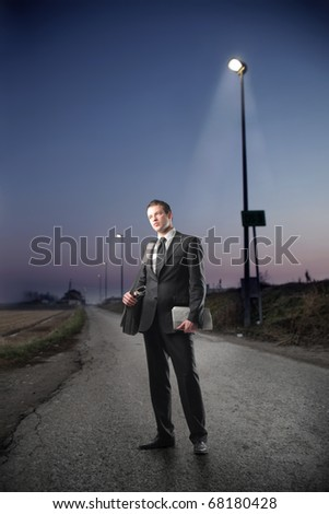 Businessman standing by night - stock photo
