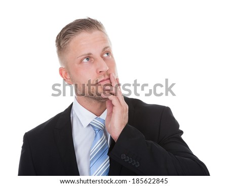 Businessman standing deep in thought with his hand to his chin looking up into the air with a look of contemplation isolated on white with copyspace