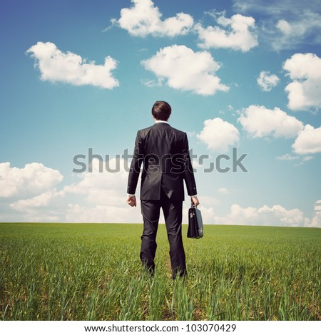 businessman standing in a field with a bag - stock photo