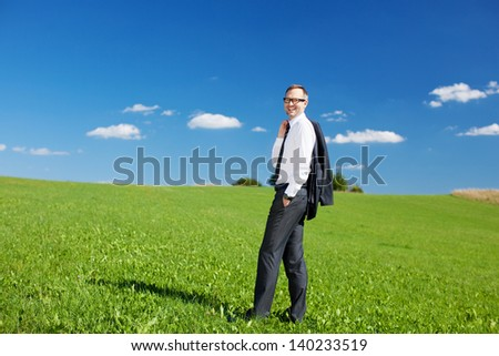 Businessman standing in a green field with his jacket slung over his shoulder enjoying the fresh air and sunshine and looking at the camera - stock photo