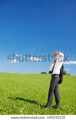 Businessman standing in a lush green field scanning the skies with his hand raised to shield his eyes - stock photo