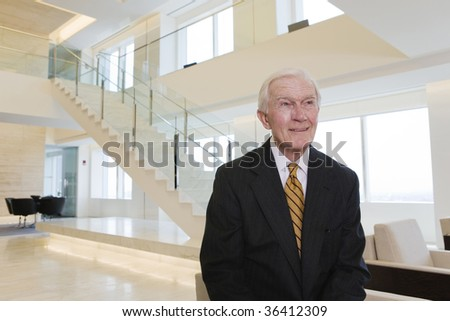 Businessman standing in a modern two story office lobby.