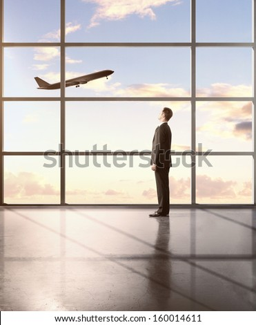 businessman standing in airport and looking in airplane
