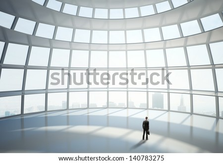 businessman standing in big hall of  hemispheric office building - stock photo