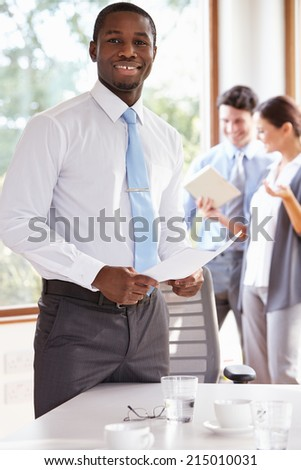 Businessman Standing In Boardroom Holding Document