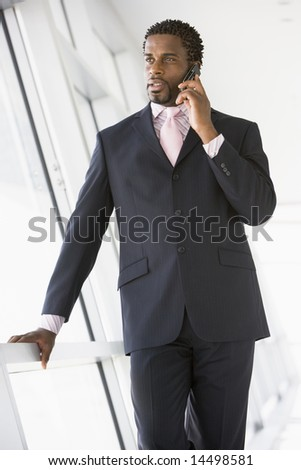Businessman standing in corridor using cellular phone - stock photo