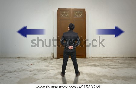 Businessman standing in doubt on the wood door,thinking the two different choices indicated by arrows pointing in opposite direction, business decision concept - stock photo