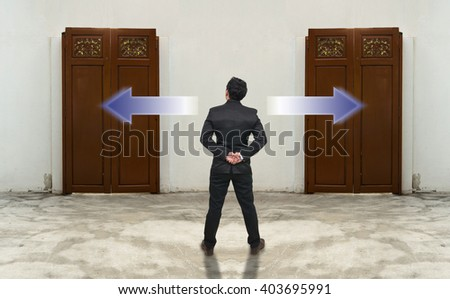Businessman standing in doubt on the wood doors,thinking the two different choices indicated by arrows pointing in opposite direction, business decision concept - stock photo